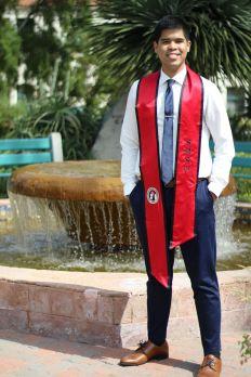 Saulon posing in his graduation stole.